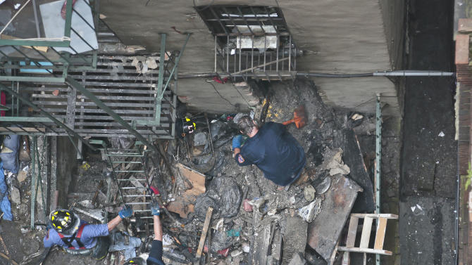 Firefighters remove debris from the back of a building in the aftermath of a fire on Thursday, July 11, 2013 in New York City's Chinatown. Twelve people were injured, three of them seriously, when an explosion inside a building led to a fire in New York City's Chinatown on Thursday, the fire department said. (AP Photo/Bebeto Matthews)