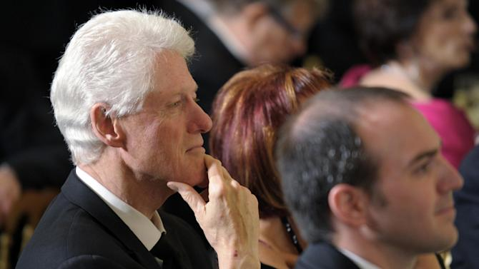 Former President Bill Clinton listens to remarks after President Barack Obama awarded Israeli President Shimon Peres with the Presidential Medal of Freedom at a dinner in the East Room of the White House in Washington, Wednesday, June 13, 2012. (AP Photo/Susan Walsh)