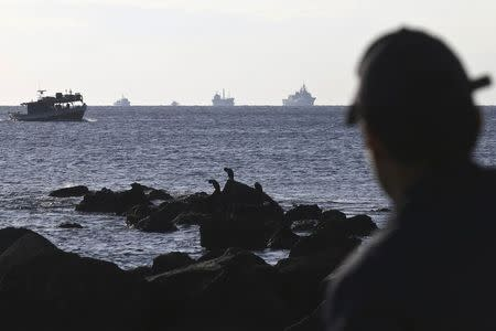 A container ship is being towed by a Greek Navy frigate as a coast guard officer looks on, at open sea a few miles southeast from the island of Crete