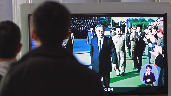 People watch TV news program showing North Korea founder late Kim Il Sung, left, and his son leader late Kim Jong Il, second from left, at Seoul Railway Station in Seoul, South Korea, Monday, April 15, 2013. Oblivious to international tensions over a possible North Korean missile launch, Pyongyang residents spilled into the streets Monday to celebrate a major national holiday, the birthday of their first leader, Kim Il Sung. (AP Photo/Ahn Young-joon)