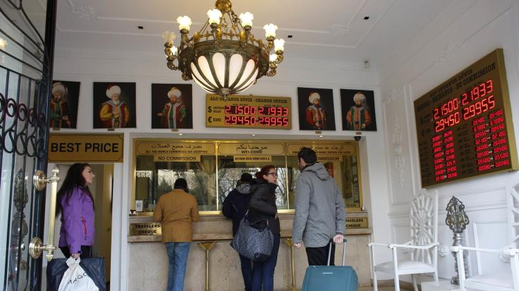 Tourists change foreign currency to Turkish Lira at a currency