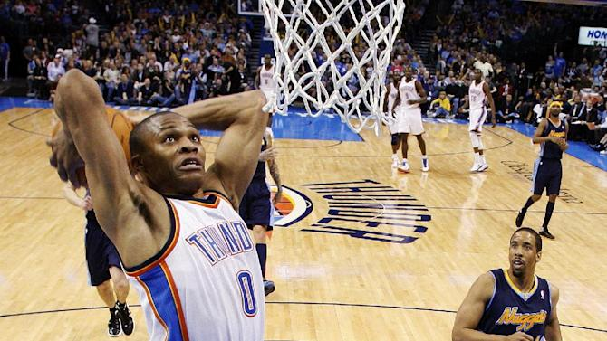 Oklahoma City Thunder guard Russell Westbrook (0) goes up for a dunk in front of Denver Nuggets guard Andre Miller, right, in the second quarter of an NBA basketball game in Oklahoma City, Sunday, Feb. 19, 2012. Oklahoma City won 124-118 in overtime. (AP Photo/Sue Ogrocki)