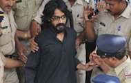 Cartoonist Aseem Trivedi, who has been arrested on sedition charges, is escorted out of the Bandra Metropolitan Magistrate court in Mumbai on September 10, 2012. India&#39;s government is facing a mounting domestic and international backlash over the arrest as critics accused it of using colonial era laws to crush dissent