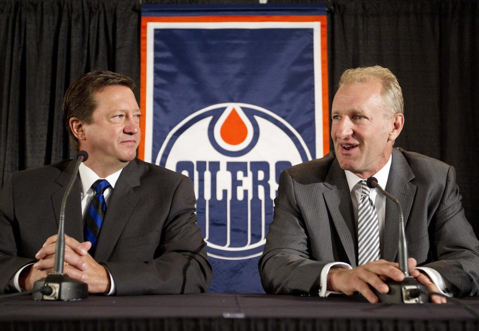 Edmonton Oilers general manager Steve Tambellini, left, announces Ralph Krueger, right, as the new head coach for the Edmonton Oilers NHL hockey team in Edmonton, Alberta, Wednesday, June 27, 2012. (AP Photo/The Canadian Press, Jason Franson)