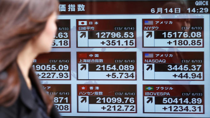 A woman looks at an electronic stock board of a securities firm in Yokohama, near Tokyo, Friday, June 14, 2013. Japan's Nikkei 225 index recovered some of its losses Friday as Asian stocks rebounded from Tokyo's sharp decline on Thursday after investors were encouraged by positive U.S. economic news. (AP Photo/Koji Sasahara)