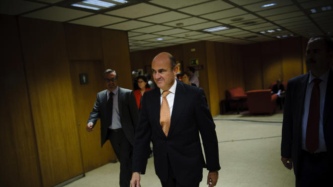 Spain's Economy Minister Luis De Guindos, center, leaves after a join press conference with European Commissioner for Economic and Monetary Affairs Olli Rehn, after a meeting at the Ministry, in Madrid, Monday, Oct. 1, 2012. (AP Photo/Daniel Ochoa De Olza)