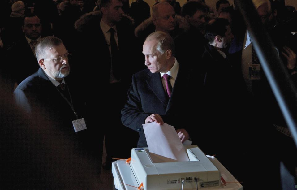 Russian Prime Minister and presidential candidate Vladimir Putin, center, casts his ballot at a polling station  in Moscow, Russia, Sunday, March 4, 2012. Polling stations have opened across Russia's vast expanse for the presidential election widely expected to return Vladimir Putin to the Kremlin. (AP Photo/Ivan Sekretarev)