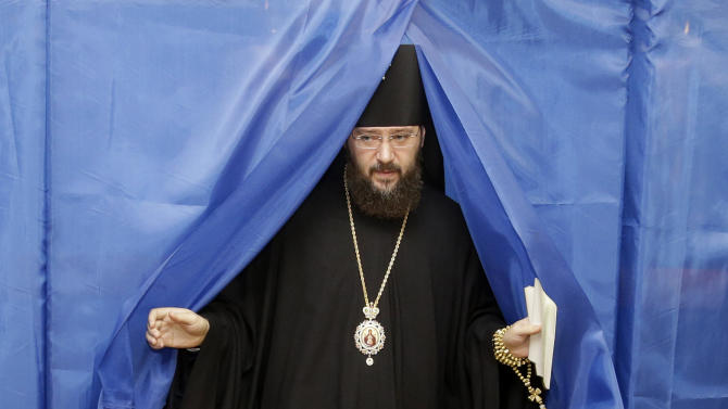 An Orthodox priest leaves a voting booth at a polling station in Kiev, Ukraine, Sunday, Oct. 28, 2012. Voters in Ukraine are choosing a new parliament Sunday. (AP Photo/Efrem Lukatsky)