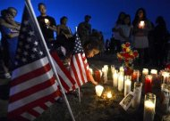 Myia Young, 4, places a candle by an American flag during a vigil for victims behind a theater where a gunman open fire at moviegoers in Aurora, Colorado July 20, 2012. REUTERS/ Jeremy Papasso