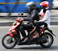 This file photo shows an Indonesian family riding on a Honda motorcycle in Jakarta. Japan's Honda Motor said on Monday that first-half net profit more than doubled to $2.7 billion, but its shares dived as the automaker warned full-year results would be much weaker than forecast
