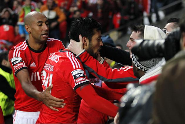 Benfica's Ezequiel Garay, centre, from Argentina, celebrates with teammate Luisao, left, from Brazil, and supporters after scoring their side's second goal against Porto during the Portuguese