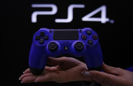 Staff at the PlayStation 4 launch event poses with the PlayStation 4's game controller before its domestic launch event at the Sony Showroom in Tokyo