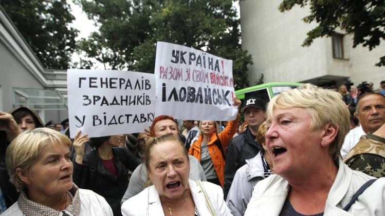 Public activists and relatives of soldiers who they say are surrounded by pro-Russian separatists in eastern Ukraine, shout slogans during a protest in front of Presidential Administration office in Kiev