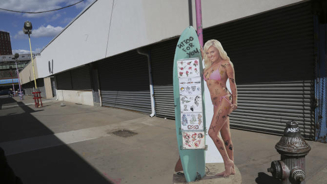 In a Saturday March 30, 2013, photo  a life size poster of a model advertising a temporary tattoo shop is framed by shuttered businesses at New York's Coney Island.  Despite making the traditional Palm Sunday opening, many of the seasonal businesses at Coney Island are still reeling from the aftermath of Superstorm Sandy. (AP Photo/Mary Altaffer)