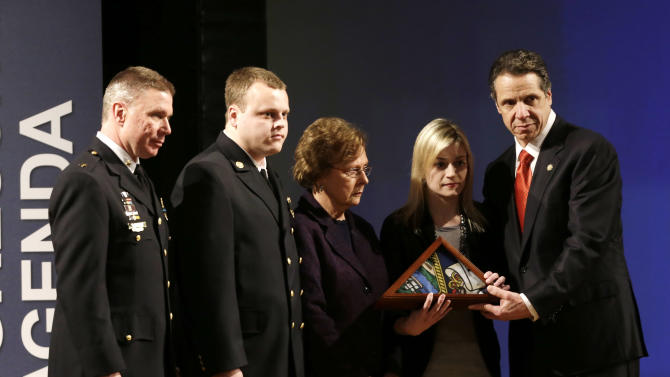 New York Gov. Andrew Cuomo presents a state flag to Kim Chiapperini, second from right, wife of slain West Webster firefighter Michael Chiapperini during his State of the State address at the Empire State Plaza Convention Center on Wednesday, Jan. 9, 2013, in Albany, N.Y. Also pictured from left are Webster Police Chief Gerald Pickering, son Nick Chiapperini and mother Marcia Chiapperini. Michael Chiapperini was killed while responding to an early-morning fire on Dec. 24, 2012. (AP Photo/Mike Groll)