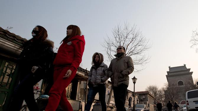 In this photo taken on Dec. 26, 2012, tourists walk past the Hutong houses near the historical Drum and Bell Tower, right in the background, in Beijing. The district government wants to demolish the scuffed courtyard homes, move their occupants to bigger apartments farther from the city center and redevelop a square in 18th century Qing Dynasty fashion. (AP Photo/Andy Wong)