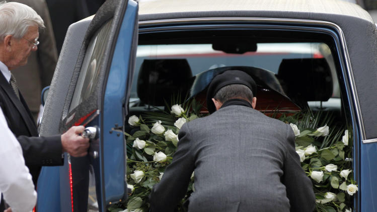 A spray of white roses is loaded into the hearse with the casket of former Penn State coach Joe Paterno after funeral services on the Penn State campus Wednesday, Jan. 25, 2012 in State College, Pa. Paterno died Sunday morning, Jan. 22. (AP Photo/Alex Brandon)