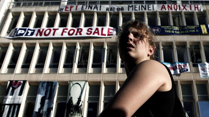 """A protester stands in front of the Greek state television ERT headquarters in Athens, on Tuesday, June 18, 2013. State TV channels in Greece remained off-air Tuesday as the political storm over the future of public broadcaster ERT rages on despite a court ruling that the prime minister's decision to pull the plug was wrong. The banner on the top reads in Greek """"ERT is, and will remain open""""(AP Photo/Petros Giannakouris)"""