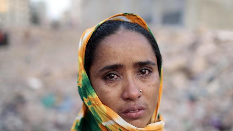 A Bangladeshi woman who lost her son in the Rana Plaza building collapse cries at the site of the accident, the worst in the history of the garment industry, on the eve of the tragedy in Savar, near Dhaka, Bangladesh, Wednesday, April 23, 2014. More than 1,100 people were killed when the illegally constructed, 8-storey building collapsed on April 24, 2013, in a heap along with thousands of workers in the five garment factories in the building. (AP Photo/A.M. Ahad)