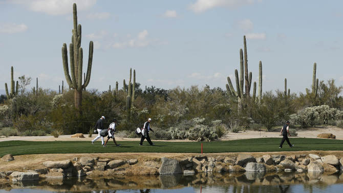 Steve Stricker, right, and Nick Watney, far left, walk around the water hazard after teeing off the fourth hole in the second round of play during the Match Play Championship golf tournament, Friday, Feb. 22, 2013, in Marana, Ariz. (AP Photo/Ross D. Franklin)