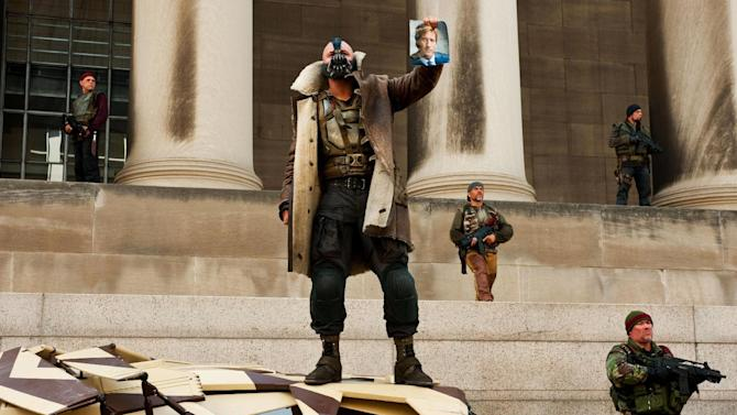 """In this publicity photo provided by Warner Bros. Pictures, Tom Hardy, center, as Bane, is shown in a scene in Warner Bros. Pictures' and Legendary Pictures' action thriller """"The Dark Knight Rises,""""  a Warner Bros. Pictures release. TM & © DC Comics. (AP Photo/Warner Bros. Pictures, Ron Phillips)"""