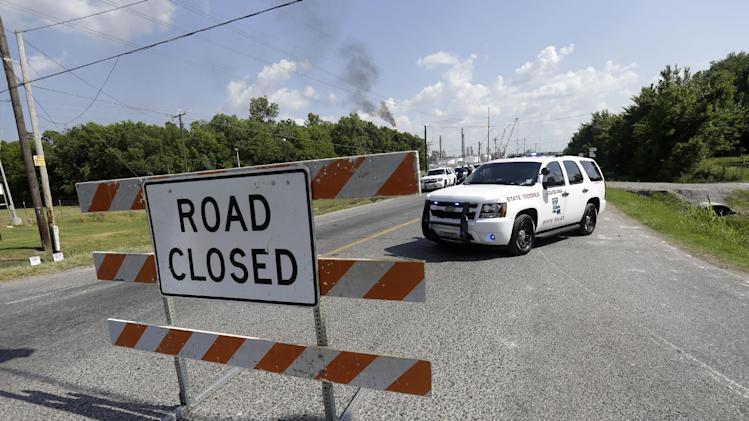 State police man a roadblock as smoke burn off from a flare at a chemical plant fire is seen about twenty miles southeast of Baton Rouge, in Geismar, La., Thursday, June 13, 2013. The plant makes highly flammable gases that are basic building blocks in the petrochemical industry. (AP Photo/Gerald Herbert)
