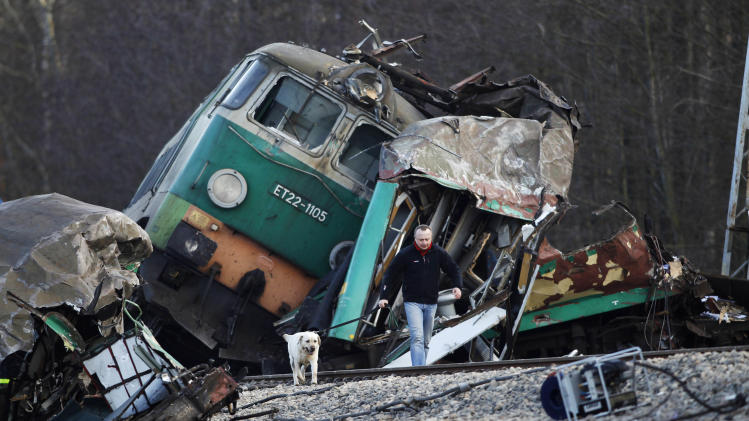 A rescue worker walks with his dog at the train crash site near the town  Szczekociny, Poland, Sunday, March 4, 2012. Two trains running on the same track collided head-on in southern Poland late Saturday, leaving more than a dozen people dead and more than 50 injured in the country's worst train disaster in more than 20 years.  (AP Photo/Petr David Josek)