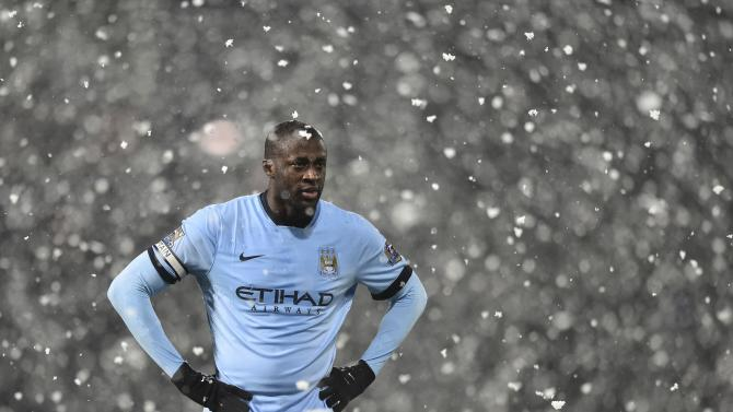 Manchester City's Yaya Toure stands in the snow during the English Premier League soccer match between Manchester City and West Bromwich Albion at The Hawthorns in West Bromwich, central England