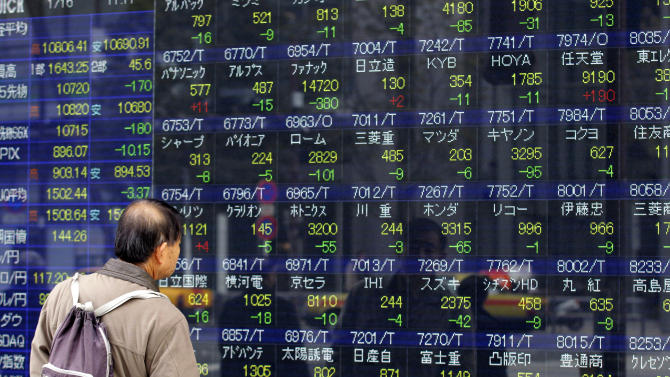 A man watches an electric price display of a securities firm in Tokyo, Wednesday, Jan. 16, 2013. Japan's benchmark index toppled off a 32-month high Wednesday after its currency's downward slide went into reverse. (AP Photo/Shizuo Kambayashi)