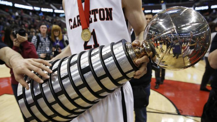 Carleton University's Smythe holds the W. P. McGee Trophy while celebrating his team's win over the University of Ottawa in Ottawa