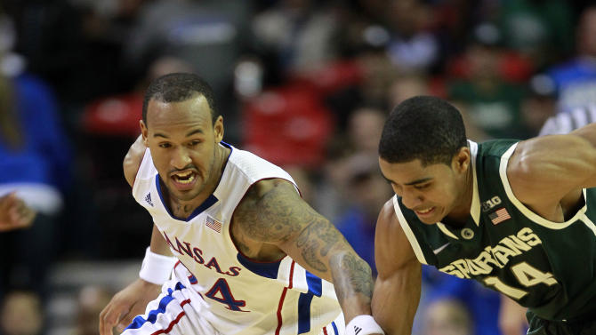 Kansas guard Travis Releford (24) and Michigan State guard Gary Harris (14) chase down a loose ball in the first half of an NCAA college basketball game in Atlanta, Tuesday, Nov. 13, 2012. (AP Photo/John Bazemore)