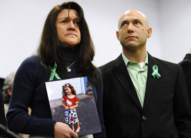 Jennifer Hensel, holding a portrait of her daughter, Sandy Hook School shooting victim Avielle Rose Richman, stands with her husband Jeremy Richman at a news conference at Edmond Town Hall in Newtown,
