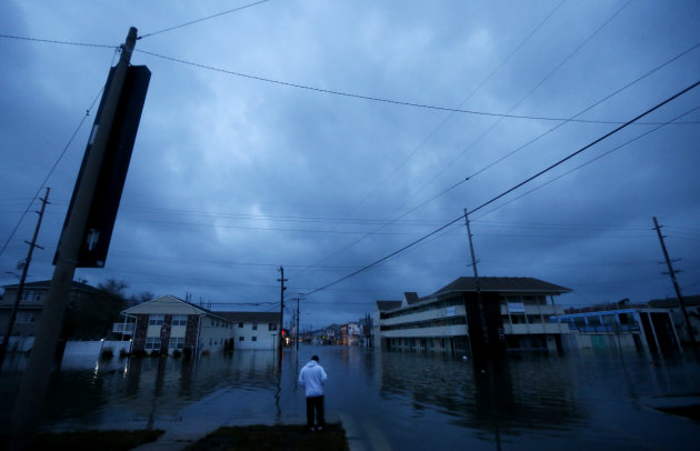 With nightfall approaching, Rodrigo Vargas, 25, of Seaside Heights, N.J., ponders treading through floodwaters to check on his second floor apartment a day after superstorm Sandy rolled through the barrier island community, Tuesday, Oct. 30, 2012. Sandy, the superstorm that made landfall Monday, caused multiple fatalities, halted mass transit and cut power to more than 6 million homes and businesses. (AP Photo/Julio Cortez)
