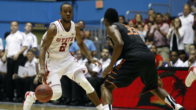 NC State's Lorenzo Brown, left, drives the ball against Oklahoma State's Marcus Smart during a NCAA college basketball game in Bayamon, Puerto Rico, Sunday, Nov. 18, 2012. (AP Photo/Ricardo Arduengo)