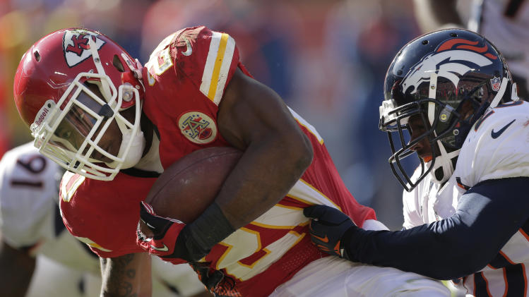 Kansas City Chiefs running back Shaun Draughn (20) is tackled by Denver Broncos strong safety Mike Adams, right, during the first half of an NFL football game at Arrowhead Stadium in Kansas City, Mo., Sunday, Nov. 25, 2012. (AP Photo/Charlie Riedel)