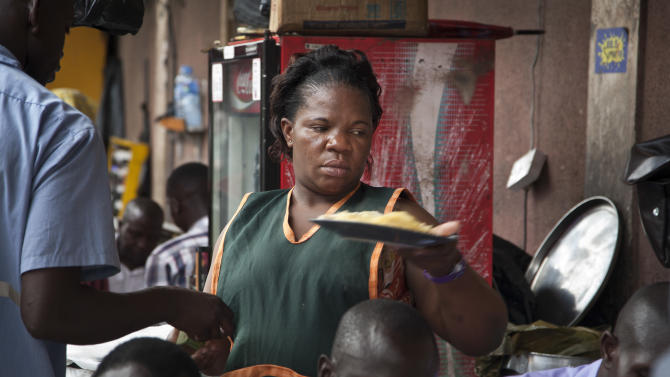 In this photo taken Friday, May 30, 2014, 34-year-old single mother Madinah Nalukenge serves dishes to customers at her food stall, frequented by transport operators, that she owns on the edge of a bus terminal in the capital Kampala, Uganda. About 63 percent of women in the non-agricultural labor force are self-employed in the informal sector in Africa, more than twice the worldwide rate according to World Bank data, which also shows that necessity, not opportunity, is the main driving force behind female entrepreneurship in poor countries. (AP Photo/Rebecca Vassie)