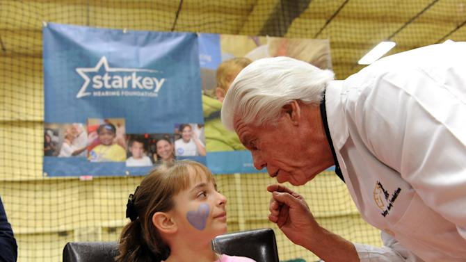 A young girl listens to Bill Austin, founder of Starkey Hearing Foundation, after he fits her with a hearing aid at The Citi Garth Brooks Super Pro Camp on Friday, Feb. 1, 2013 in New Orleans. (Photo by Cheryl Gerber/Invision for Starkey Hearing Foundation/AP Images)