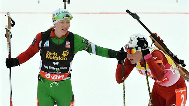 Darya Domracheva of Belarus (l) greets second placed Tora Berger of Norway after the women's 12.5km mass start