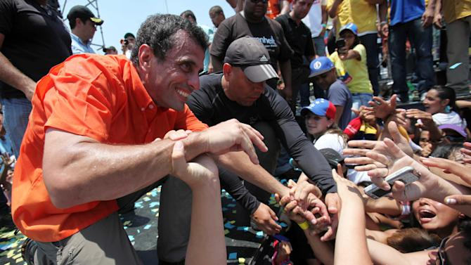Opposition presidential candidate Henrique Capriles greets supporters during a campaign rally in San Fernando de Apure, Venezuela, Thursday, April 11, 2013. Capriles is running against the ruling party candidate and Nicolas Maduro in the upcomong April 14 presidential election. (AP Photo/Fernando Llano)