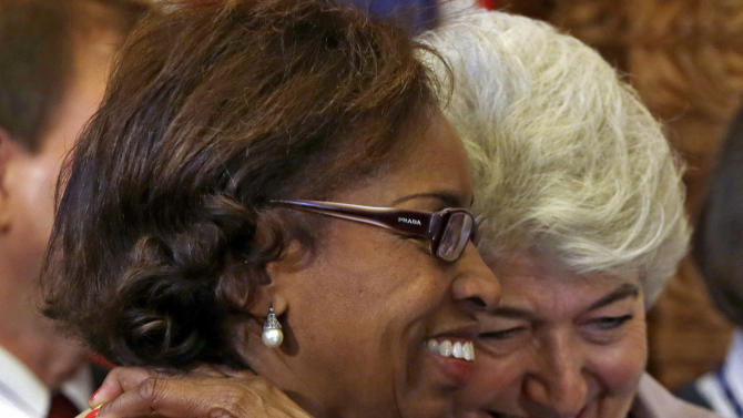 Rep. Rhonda Fields, left, D-Aurora, and Rep. Lois Court, D-Denver, embrace after Colorado Gov. John Hickenlooper signed gun control bills into law at the Capitol in Denver on Wednesday, March 20, 2013. (AP Photo/Ed Andrieski, Pool)