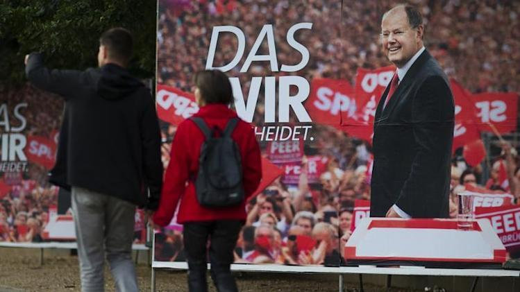 People walk past an election campaign poster of Steinbrueck, the chancellor candidate of the Social Democratic Party, in Berlin