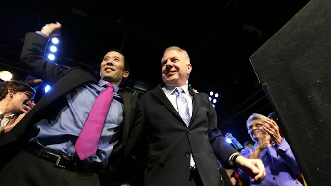 Seattle mayoral candidate state Sen. Ed Murray, center, is cheered by his husband, Michael Shiosaki, left, and former Gov. Chris Gregoire at an election night party Tuesday, Nov. 5, 2013, in Seattle. Murray challenged incumbent Mayor Mike McGinn in a race where both candidates have been trying to establish themselves as the more liberal choice for voters in the Northwest's largest city. (AP Photo/Elaine Thompson)