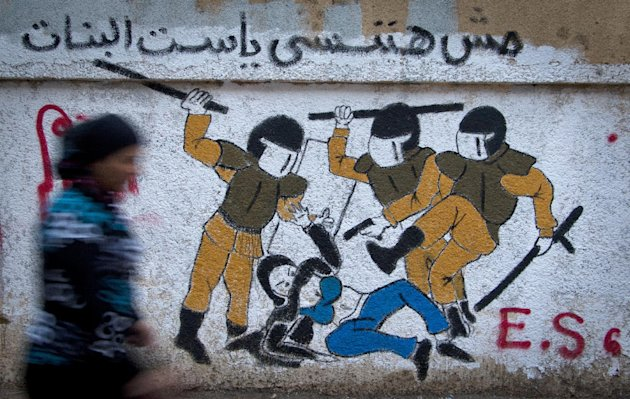 "An Egyptian woman passes by a new mural inspired by a widely circulated photo of Egyptian police beating and stripping a veiled female protester, on a recently whitewashed wall in Tahrir Square, Cairo, Egypt, Friday, Sept. 28, 2012. The Arabic writing reads, ""we will not forget you.""(AP Photo/Khalil Hamra)"