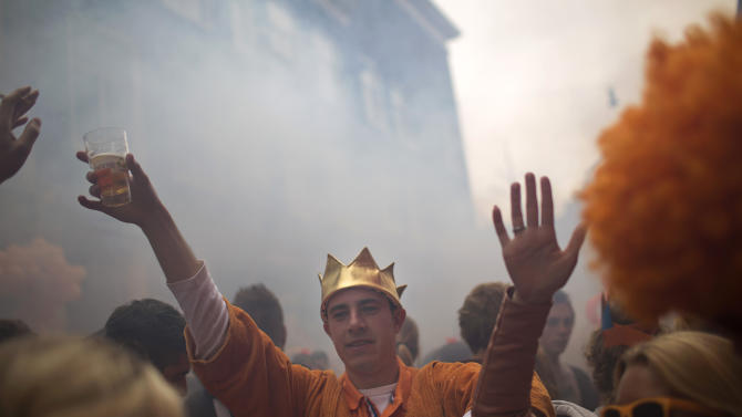 People dance in the street in Amsterdam as they celebrate the coronation of King Willem-Alexander, Tuesday, April 30, 2013. Millions of Dutch people dressed in orange flocked to celebrations around the Netherlands Tuesday in honor of a once-in-a-generation milestone for the country's ruling House of Orange-Nassau: after a 33-year reign, Queen Beatrix abdicated in favor of her eldest son, Willem-Alexander. (AP Photo/Emilio Morenatti)