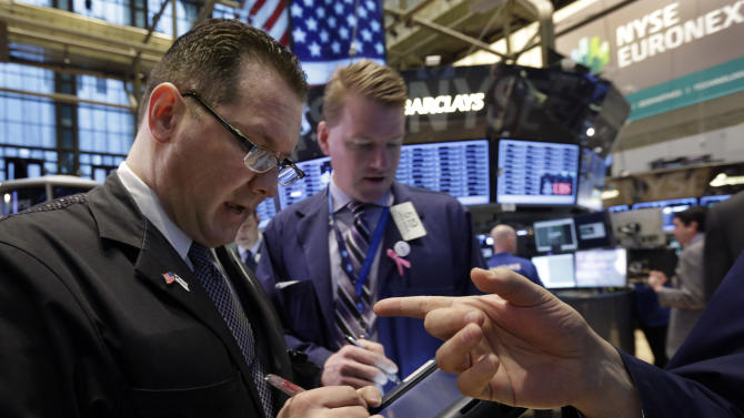 In this Monday, Feb. 25, 2013, photo, Trader Edward Curran, left, works on the floor of the New York Stock Exchange. Uncertainty over the outcome of a budget battle in Washington pushed world stock markets lower on Monday March 4, 2013. (AP Photo/Richard Drew)