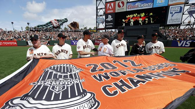 San Francisco Giants fans and players, including starting pitcher Tim Lincecum, second from left, right fielder Hunter Pence, center, manager Bruce Bochy, third from right, and starting pitcher Ryan Vogelsong, far right, unveil  the team's 2012 World Championship flag before a baseball game against the St. Louis Cardinals, Friday, April 5, 2013, in San Francisco. (AP Photo/Marcio Jose Sanchez, Pool)