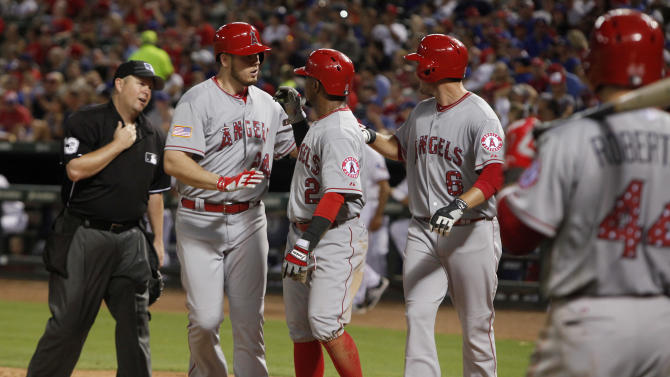 Los Angeles Angels' C.J. Cron, left, is met at home by Erick Aybar and David Freese (6) after his three-run home run in the sixth inning of a baseball game against the Texas Rangers, in Arlington, Texas, on Saturday, July 4, 2015. The Angels won 13-0. (AP Photo/Brad Loper)