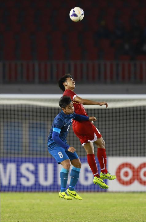 Abu Sujad of Singapore and Theerathon Bunmathan of Thailand fight for ball during the soccer semi-final match at the 27th SEA Games in Naypyitaw