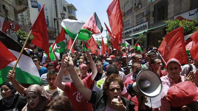 Palestinians wave national and PFLP flags during a protest in the West Bank city of Ramallah Sunday, July 28, 2013. Some two hundred supporters of the Popular Front for the Liberation of Palestine protested against the resuming of the peace talks with Israel. (AP Photo/Majdi Mohammed)