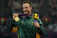 South Africa's Oscar Pistorius poses on the podium with his gold medal after winning the men's 400m - T44 final at the London 2012 Paralympic Games on September 8, 2012. The sports world reacted with a mix of shocked horror and caution Thursday to news that popular South African Oscar Pistorius had been charged with gunning down his model girlfriend